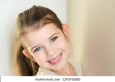 portrait of a little caucasian white beautiful brunette girl with pony tail on neutral background. smiling toothless green eyed happy girl with cute protruding ears. Kid expression portrait with