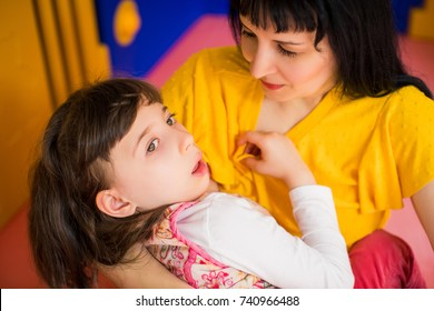 Portrait of little charming disabled girl who lying in her mother's arms in the room