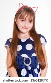Portrait of a little cheerful girl with cat ears and in a polka dot dress
