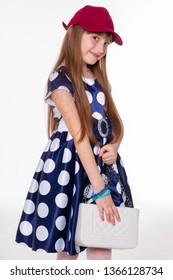Portrait of a little cheerful girl in a polka dot dress and red cap