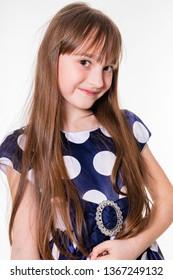 Portrait of a little cheerful girl in a polka dot dress