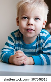 Portrait of a little, cheerful, two years old boy who's looking at something what is far away from him.