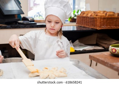 Portrait of a little chef cooking girl