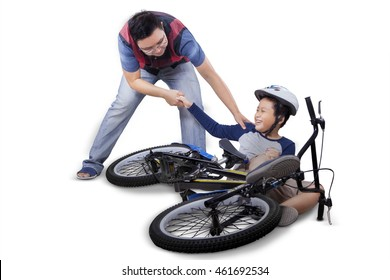 Portrait of little child learn to ride a bike and falling off, crying and get help from his father