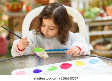 Portrait of little child painting, summer outdoor.Kid drawing on a stone.