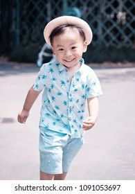 Portrait of a little Chinese boy, two years old, smiling and running outside in sunny summer day, funny happy healthy toddler.
