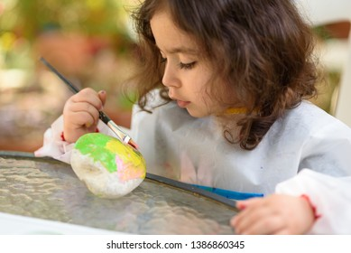 Portrait of little curly child painting, summer outdoor.Kid drawing on a stone.