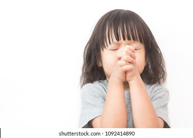 Portrait of little cute asian girl praying, young girl with her hands together isolated on white background, close up expression. Religion believe hope pray stressful concept