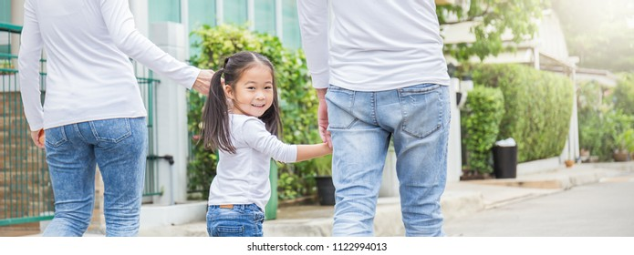Portrait of little cute asian girl holding her father mother hands in the park. Together family's day love education home school concept panoramic banner