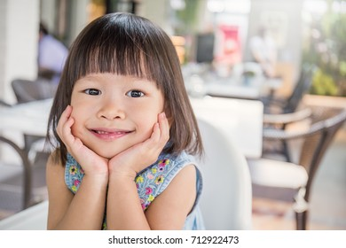 Portrait of little cute asian girl, lovely small asian girl with her hands holding her cheeks, happy and fun expression