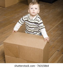 portrait of little cute boy playing with box