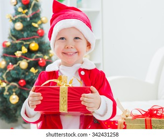 Portrait of little cute boy in Santa hat drinking milk with biscuit