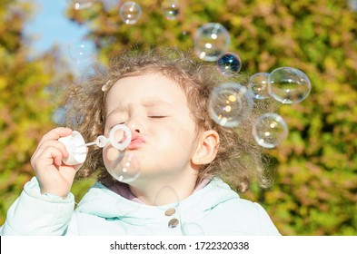 portrait little cute girl blows soap bubbles. happy child plays outside. baby plays outdoors in nature.