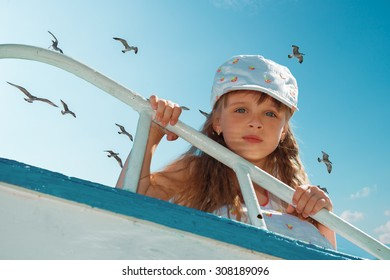 Portrait of little cute girl enjoying playing on boat on a hot sunny day. Seagulls in the sky.