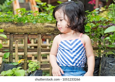 Portrait of a little cute girl in the garden sorrounded by tropical plants