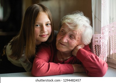 Portrait of little cute girl and her elderly grandmother.