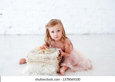 Portrait of a little cute girl with long hair and elegamt dress on a white background.
