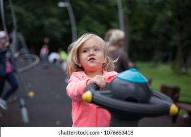 Portrait of a little cute girl playing in the playground in park, having fun. Game and outdoor play concept.