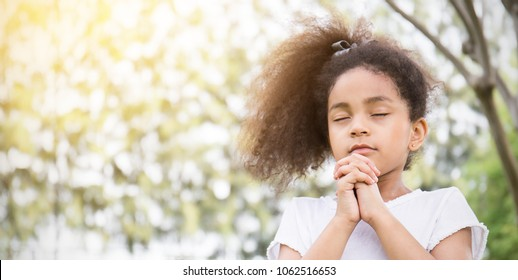 Portrait of little cute girl praying in the park, young girl with her hands together, closeup expression. Religion faith and believe concept banner