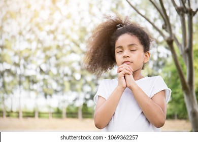 Portrait of little cute girl praying in the park, young girl with her hands together, closeup expression. Religion faith and believe concept