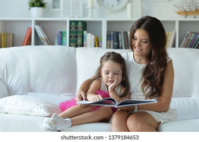 Portrait of little cute girl reading book with mother while sitting on safe