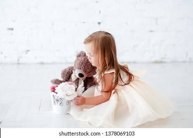 Portrait of a little cute girl with a soft toy and flowers on a white background