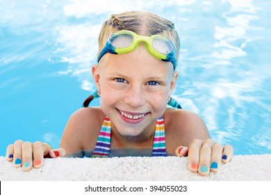 Portrait of little cute girl in the swimming pool. Sunny summer day