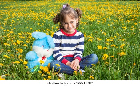 Portrait of little cute girl with toy rabbit on background dandelions