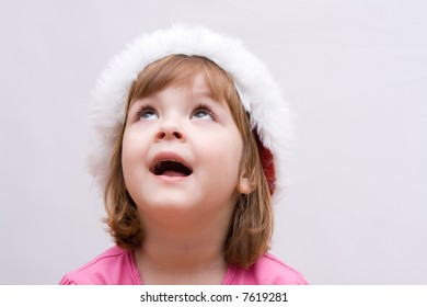 portrait of little, cute girl wearing Santa Claus hat
