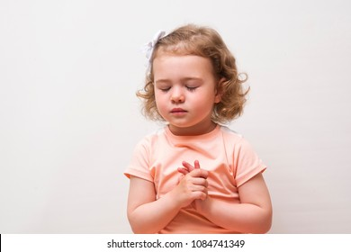 Portrait of little cute girl who prays or dreams on a white background