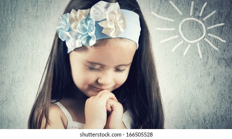 Portrait of little cute girl who prays or dreams