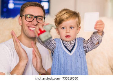 Portrait of little cute serious boy who holding card and toy in hands near his smiling father who clapping in the palm at home