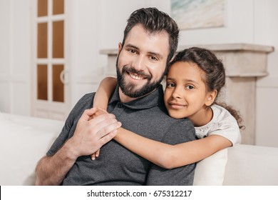 portrait of little daughter hugging smiling father, multicultural family at home