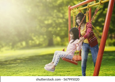 Portrait of little daughter and mother playing swing in the park while smiling together