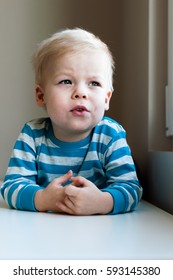 Portrait of little, dreamy, lost in thoughts and cheerful two years old boy.