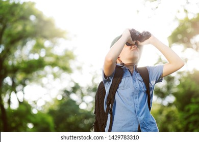 Portrait of little explorer with binoculars in forest. Boy traveler in helmet play in the park. Happy child go hiking with backpack in summer nature.