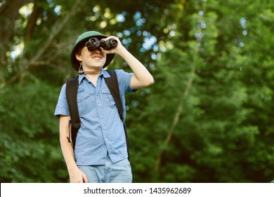Portrait of little explorer with binoculars in forest. Boy traveler in helmet play in the park. Happy child go hiking with backpack in summer nature. Dream concept.