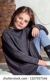 Portrait little fashion kid. Children's fashion concept. Stylish little little hipster girl looks confident, defiant. Beautiful face caucasian child. hands on her knees.