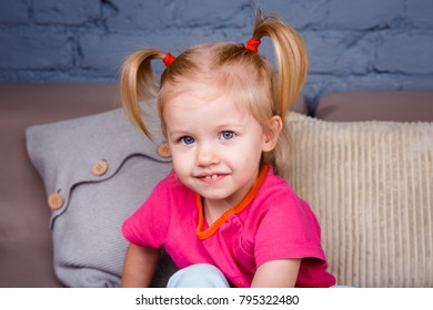 portrait of a little funny blonde girl with blue eyes and a funny hairdo dabbles and plays on the sofa at home. He laughs showing his tongue and teeth. She is dressed in bright stylish clothes.