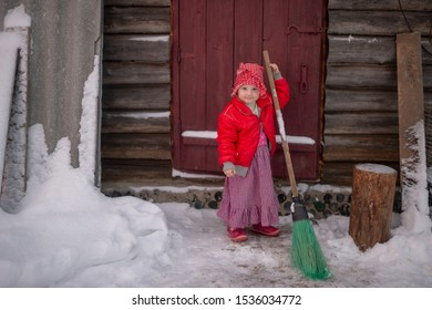 Portrait of little funny girl dressed like an old witch posing with broom in front of a wooden door in snowy winter day.