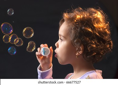 portrait of little girl, 5-6 years old, blowing soap bubbles