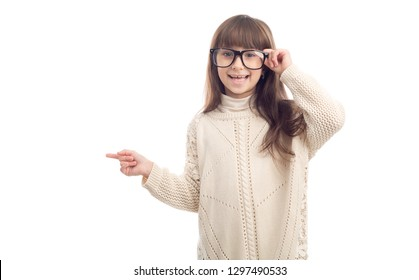 Portrait of a little girl of 7 years old with glasses points finger towards left.