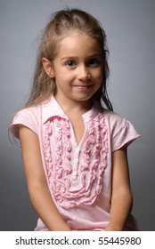 Portrait of a little girl against grey background looking at the camera smiling looking sideways