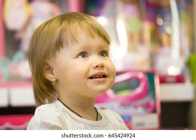 Portrait of the little girl among toys in children store
