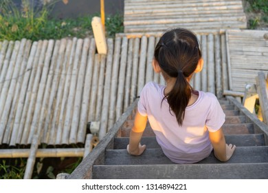 Portrait little girl Asian Back Sitting on the stairs