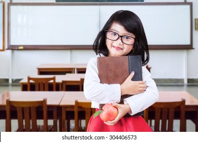 Portrait of little girl back to school and standing in the classroom while wearing glasses and holding a book with apple
