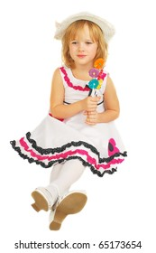 Portrait of little girl in beautiful dress sitting  with lollipops  isolated on the white background. Nice Easter image.