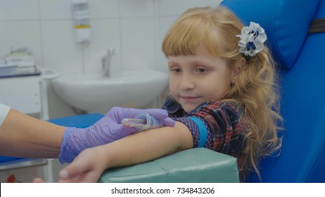Portrait of little girl at blood test. Nurse is taking blood sample in medical surgery from a vein in the arm. Child looking on the tube.