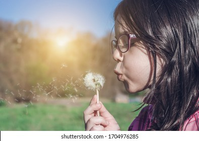 Portrait of little girl blowing a dandelion flower outdoor. Side view of female child playing outside. Spring time, pollen allergy concept.