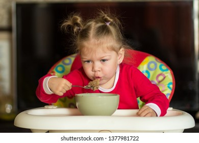 Portrait of  little girl blowing on hot porridge to cool sitting in a feeding chair